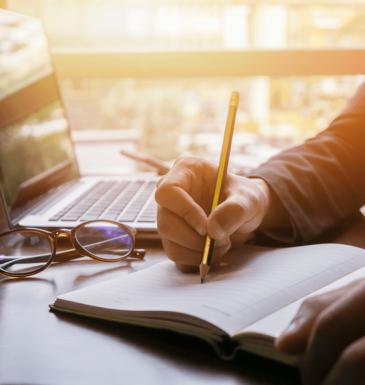 Imagem mostra uma mão com um lápis escrevendo em um caderno